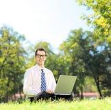Hombre de negocios joven que se sienta en una hierba y que trabaja en un ordenador portátil Imagen de archivo