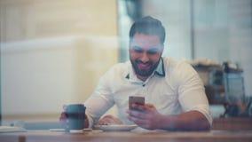 Hombre de negocios joven que se sienta en una tabla en un café usando iphone y la risa Gente acertada, rutina diaria entertaining almacen de video
