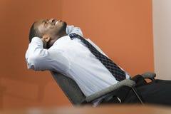 Hombre de negocios joven que sonríe, estirando e inclinándose. Fotografía de archivo
