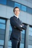 Hombre de negocios joven que sonríe al aire libre con los brazos cruzados Imagen de archivo libre de regalías