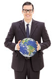 Hombre de negocios joven que sostiene el mundo Imagenes de archivo