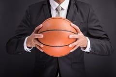 Hombre de negocios joven que sostiene la bola del baloncesto Imagenes de archivo