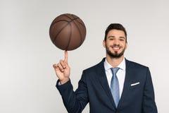 hombre de negocios joven que sostiene la bola del baloncesto en el finger y que sonríe en la cámara Foto de archivo libre de regalías