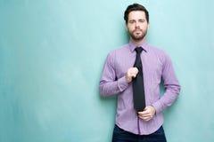 Hombre de negocios joven que sostiene la corbata Imagen de archivo