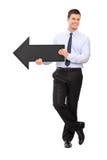 Hombre de negocios joven que sostiene la flecha negra que señala a la derecha Foto de archivo