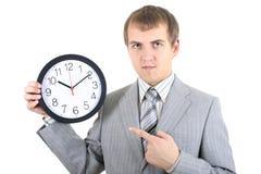 Hombre de negocios joven que sostiene un reloj Foto de archivo libre de regalías
