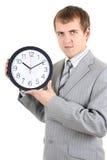 Hombre de negocios joven que sostiene un reloj Imagenes de archivo