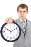 Hombre de negocios joven que sostiene un reloj Fotos de archivo libres de regalías