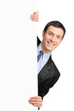 Hombre de negocios joven que sostiene una cartelera en blanco Imágenes de archivo libres de regalías