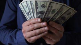 Hombre de negocios joven que sostiene una fan de cientos billetes de dólar almacen de video