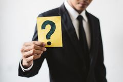 Hombre de negocios joven que sostiene una tarjeta con el SIGNO de INTERROGACIÓN imagen de archivo libre de regalías