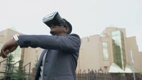 Hombre de negocios joven que tiene experiencia de VR usando las auriculares de la realidad virtual 360 al aire libre