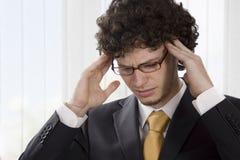 Hombre de negocios joven que tiene un dolor de cabeza Imagen de archivo libre de regalías