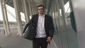 Hombre de negocios joven que tira de la maleta en terminal de aeropuerto moderno Concepto del individuo que viaja metrajes