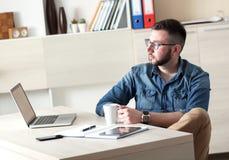 Hombre de negocios joven que toma el descanso para tomar café en su oficina Fotos de archivo