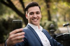Hombre de negocios joven que toma un selfie con su smartphone en el parque Fotografía de archivo libre de regalías