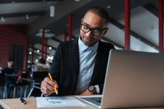 Hombre de negocios joven que trabaja con el ordenador portátil imagen de archivo