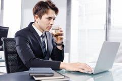 Hombre de negocios joven que trabaja con el ordenador portátil en oficina imagenes de archivo