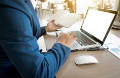 Hombre de negocios joven que trabaja con el ordenador portátil, notas de libro, las manos del hombre imagen de archivo libre de regalías