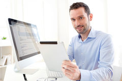 Hombre de negocios joven que trabaja en casa en su tableta Foto de archivo