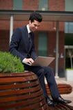 Hombre de negocios joven que trabaja en el ordenador portátil fuera de la oficina Fotos de archivo libres de regalías