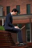 Hombre de negocios joven que trabaja en el ordenador portátil fuera de la oficina Foto de archivo libre de regalías
