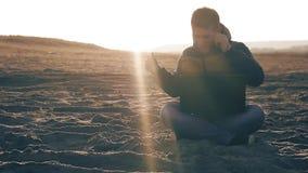 Hombre de negocios joven que trabaja en el ordenador portátil en la playa en el freelancer en línea del viajero del trabajo indep almacen de video