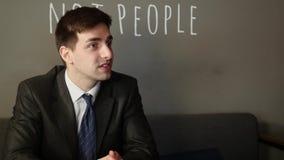 Hombre de negocios joven que trabaja en el ordenador portátil y que habla con el cliente, en la tabla en el café almacen de video