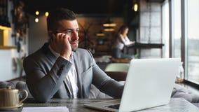 Hombre de negocios joven que trabaja en el ordenador portátil y que habla en el teléfono, en la tabla en el café metrajes