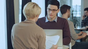 Hombre de negocios joven que trabaja en el ordenador portátil y la empresaria que trabajan con los documentos que se sientan en e almacen de metraje de vídeo
