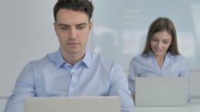 Hombre de negocios joven que trabaja en el ordenador port?til en oficina metrajes