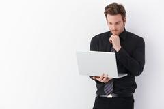 Hombre de negocios joven que trabaja en la computadora portátil Foto de archivo