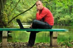 Hombre de negocios joven que trabaja en la computadora portátil al aire libre Imagenes de archivo
