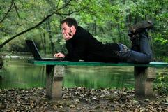 Hombre de negocios joven que trabaja en la computadora portátil al aire libre Fotografía de archivo libre de regalías