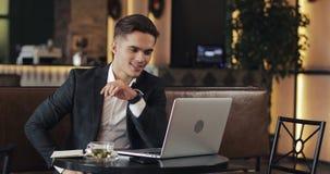 Hombre de negocios joven que trabaja en oficina moderna o co-que trabaja y que usa el reloj elegante Freelancer que habla con un  almacen de video