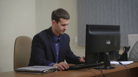 Hombre de negocios joven que trabaja en oficina, sentándose en el escritorio, mirando la pantalla de ordenador almacen de metraje de vídeo
