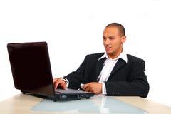 Hombre de negocios joven que trabaja en su computadora portátil Fotografía de archivo libre de regalías