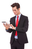 Hombre de negocios joven que trabaja en su pista de la tablilla Fotografía de archivo libre de regalías