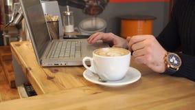 Hombre de negocios joven que trabaja en una cafetería con un ordenador portátil almacen de metraje de vídeo