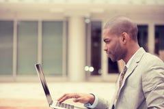 Hombre de negocios joven que trabaja usando el ordenador portátil al aire libre Fotos de archivo libres de regalías
