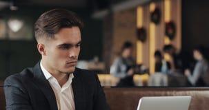 Hombre de negocios joven que usa el ordenador portátil que se sienta en la tabla del café almacen de video