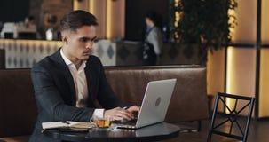 Hombre de negocios joven que usa el ordenador portátil que se sienta en la tabla del café metrajes