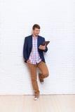 Hombre de negocios joven que usa el soporte social de la comunicación de la red de la tableta sobre la pared Imagen de archivo