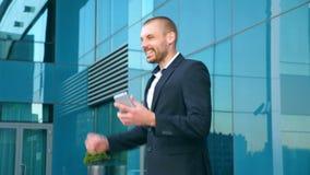 Hombre de negocios joven que usa el teléfono elegante cerca de oficina y celebrando el logro El hombre de negocios leyó buenas no almacen de video