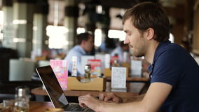 Hombre de negocios joven que usa en el ordenador portátil en café metrajes