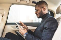 Hombre de negocios joven que usa la tableta mientras que se sienta en el asiento trasero de un coche fotos de archivo