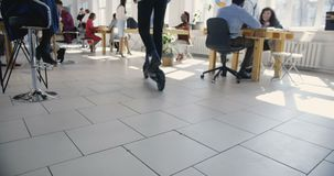Hombre de negocios joven que usa la vespa eléctrica para moverse alrededor de oficina de moda moderna Atmósfera multiétnica sana  almacen de video