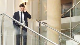 Hombre de negocios joven que usa smartphone abajo de las escaleras en oficina moderna metrajes