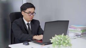 Hombre de negocios joven que usa un ordenador portátil almacen de video