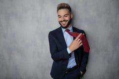 Hombre de negocios joven relajado que juega con su lazo y risas imagen de archivo libre de regalías